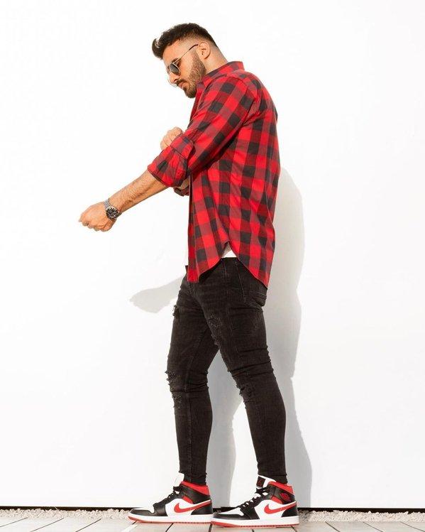 Look de hombre con camisa estampada a cuadros roja y negra y pantalones vaqueros ajustados negros
