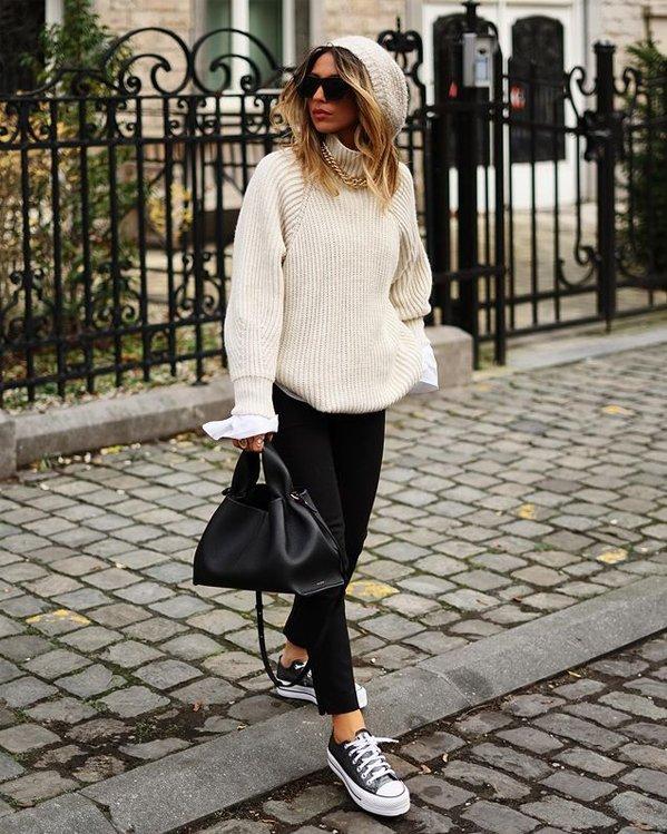 Look de mujer con jersey oversize, pantalón vaquero negro ajustado y zapatillas casual negras
