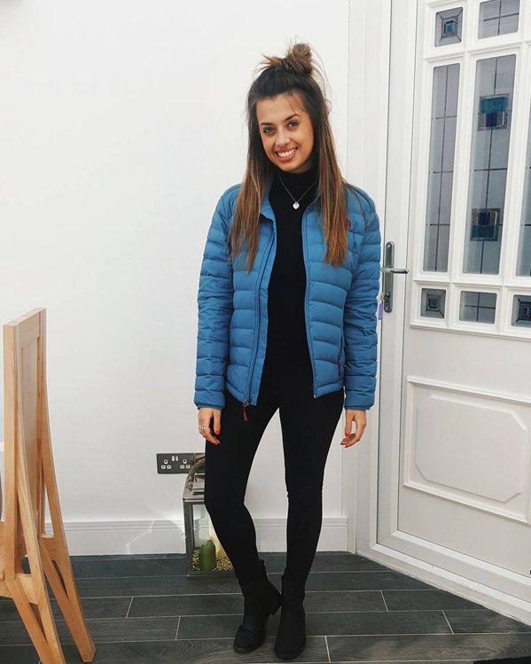 Look mujer tendencia moda con parka acolchada azul, jeans ajustados negros y botines negros de suela plana