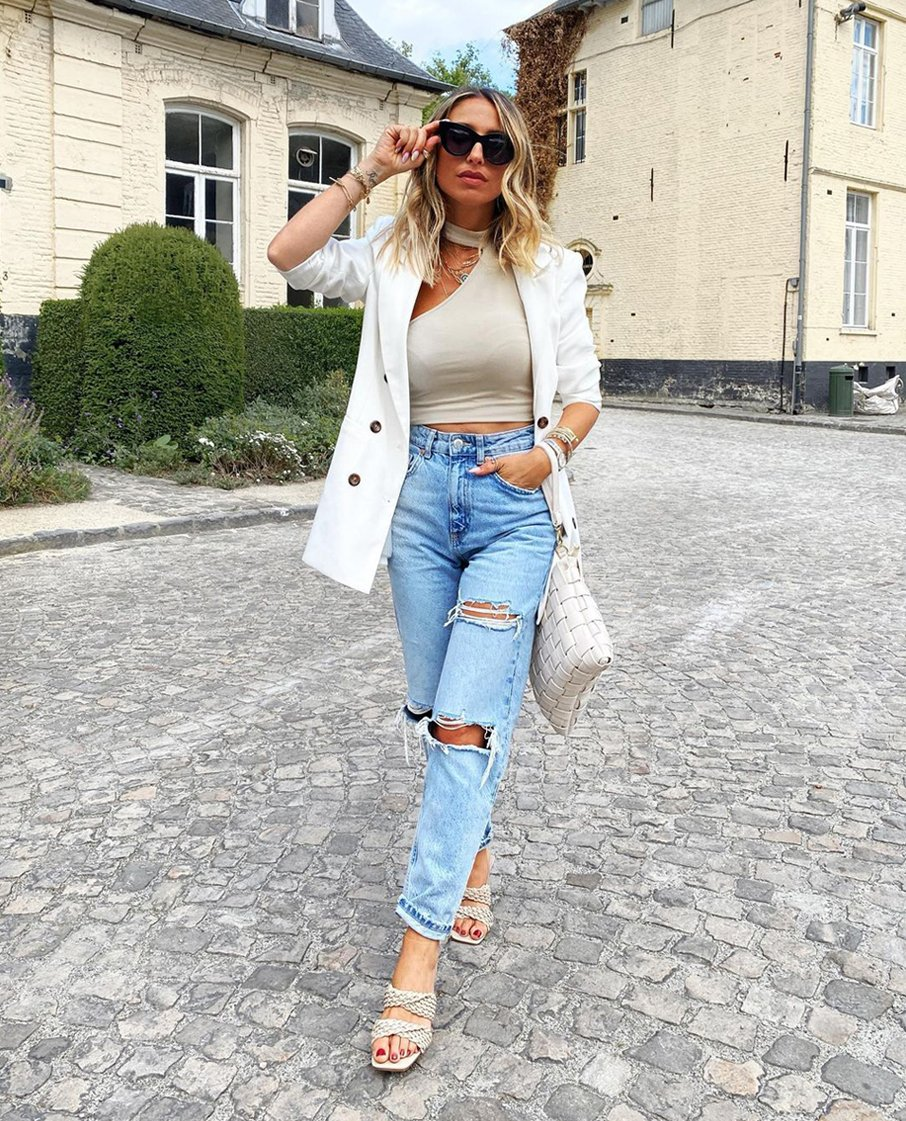 Outfit con pantalón vaquero descosido y chaqueta blanca