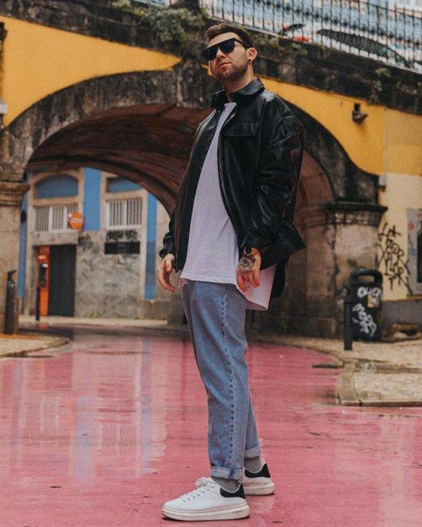 Outfit de hombres con pantalones vaqueros anchos, camiseta y chaqueta de piel sintética negra
