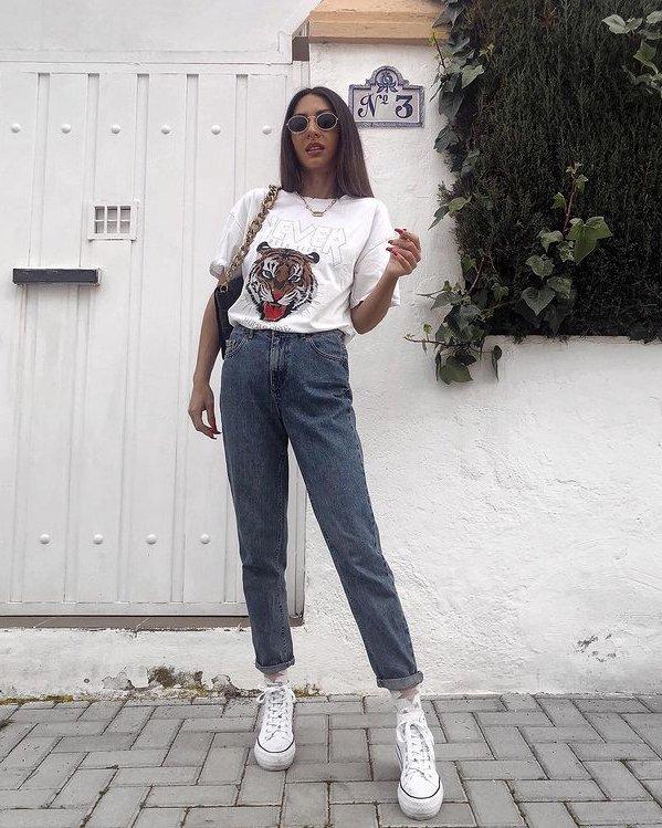 Outfit de mujer con camiseta con dibujo, jeans rectos de cintura alta y zapatillas blancas