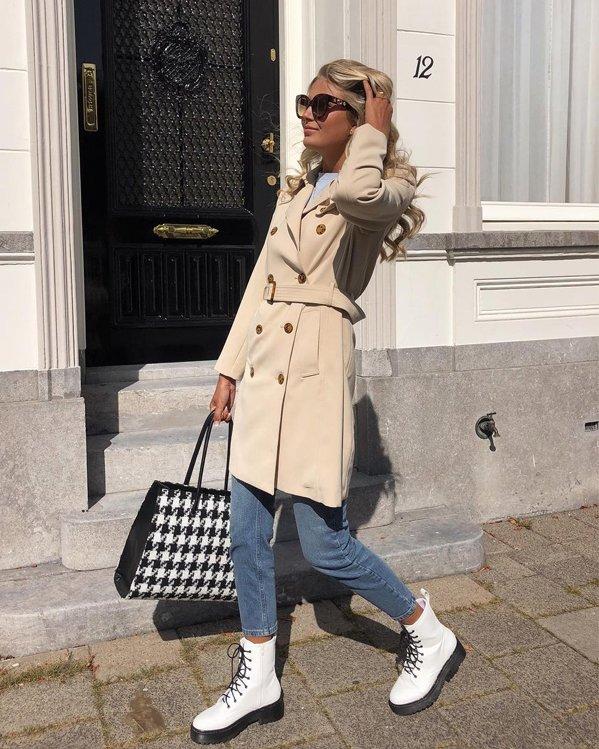 Outfit elegante casual de mujer con gabardina camel con botones, pantalón vaquero informal y botas blancas de suela gruesa