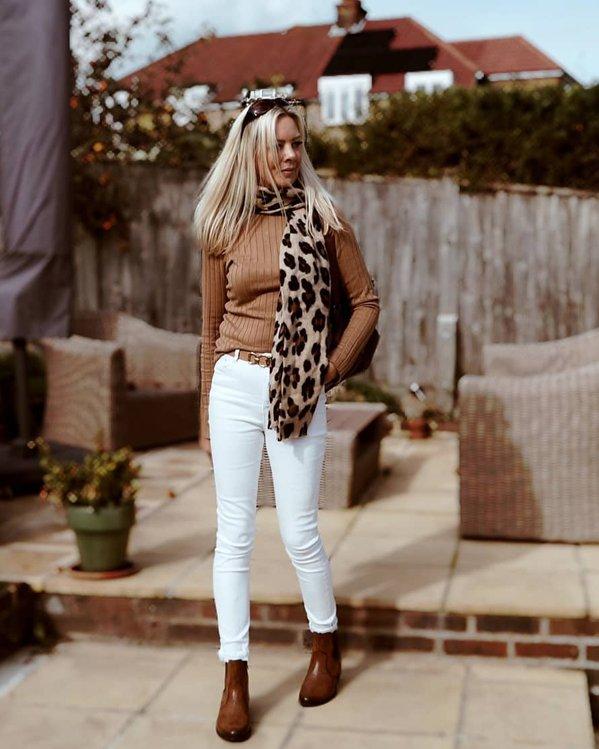 Outfit elegante de mujer con jersey marrón de canalé, pantalones blancos ajustados y botines marrones