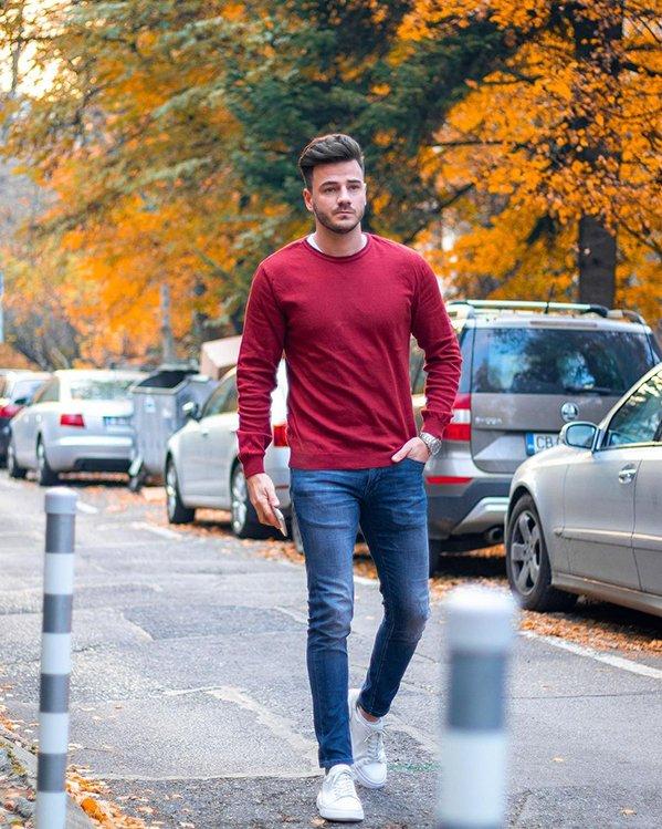 Outfit hombre juvenil con jersey rojo, jeans azules y zapatillas deportivas