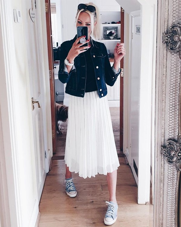 Outfit informal para mujer con chaqueta vaquera, falda plisada blanca por debajo de las rodillas y zapatillas Converse planas en azul claro