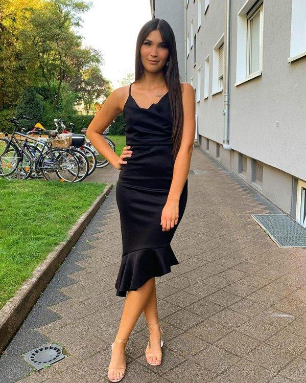 Outfit para fiesta elegante de mujer con vestido negro asimétrico y sandalias transparentes de tacón