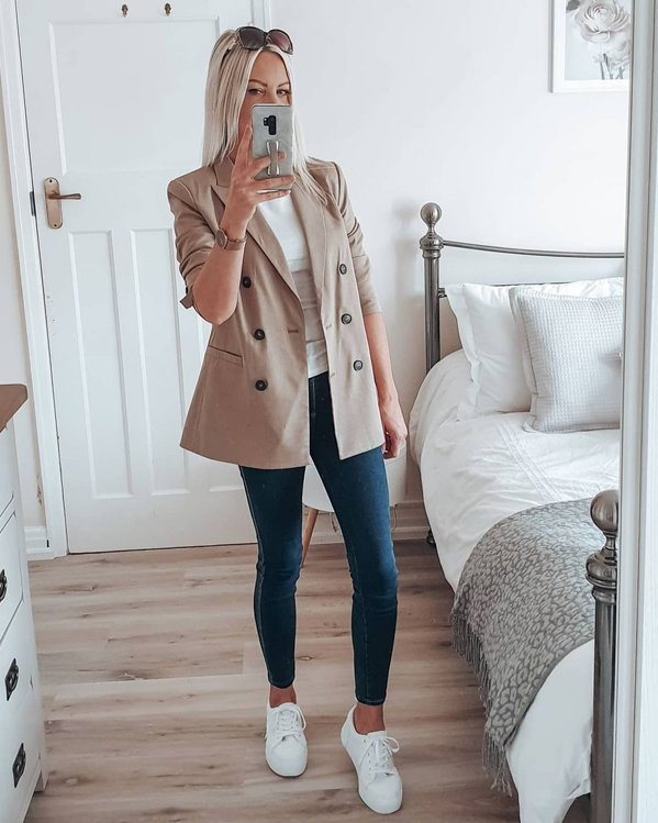 Outfit para mujer con blazer color camel, camiseta, jeans ajustados y bambas blancas