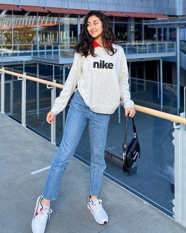 Outfits deportivos mujer con sudadera básica gris, pantalones vaqueros rígidos y sneakers blancos