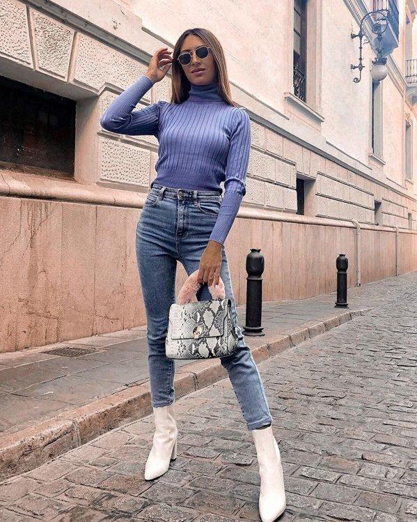 Outfits informales para chicas con jersey morado en punto de canalé, jeans ajustados y botines blancos con tacón