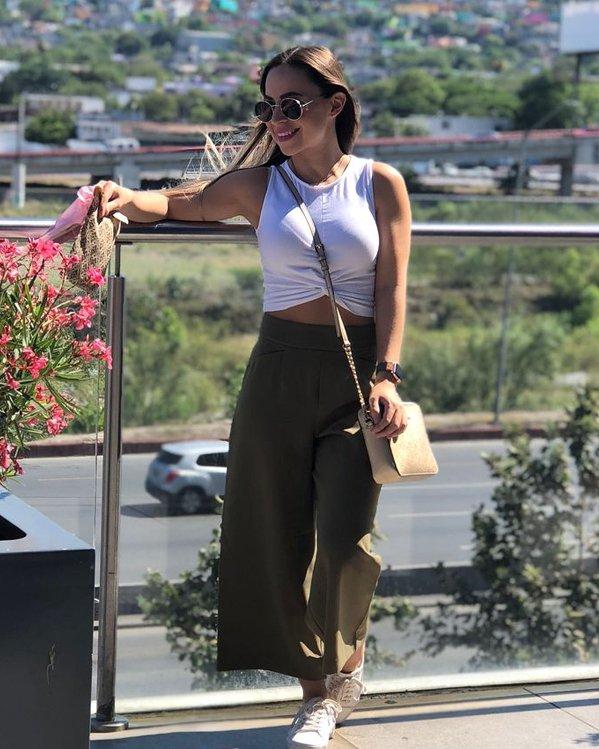 Outfits streetwear de mujer formado por un top sin mangas corto en blanco, pantalón suelto de pernera ancha en khaki y bambas blancas